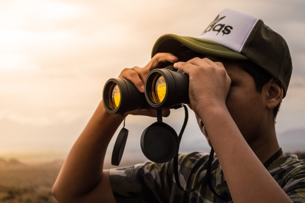 Guy looking in binoculars (Discovery can Overcome Loneliness)