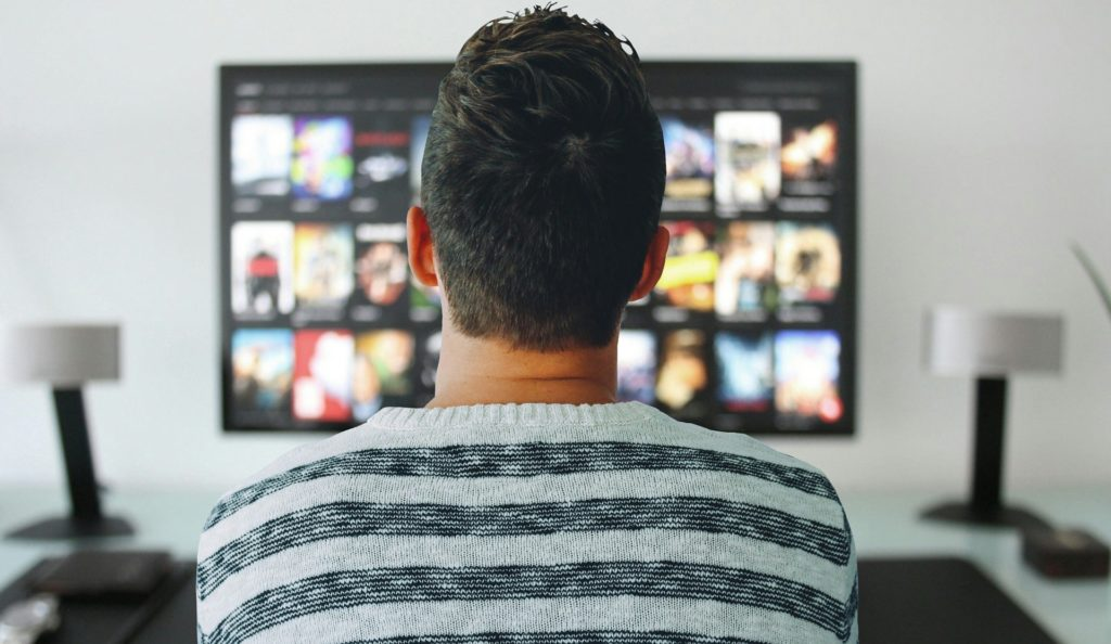 Guy watching comedy or feel good movies.